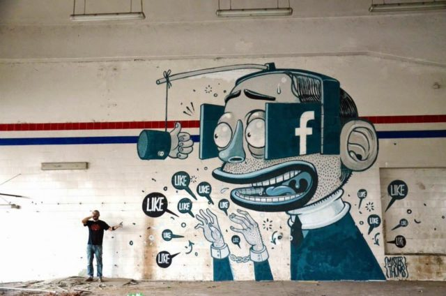 Cartoony Mural Depicts Man Obsessing over Facebook Likes