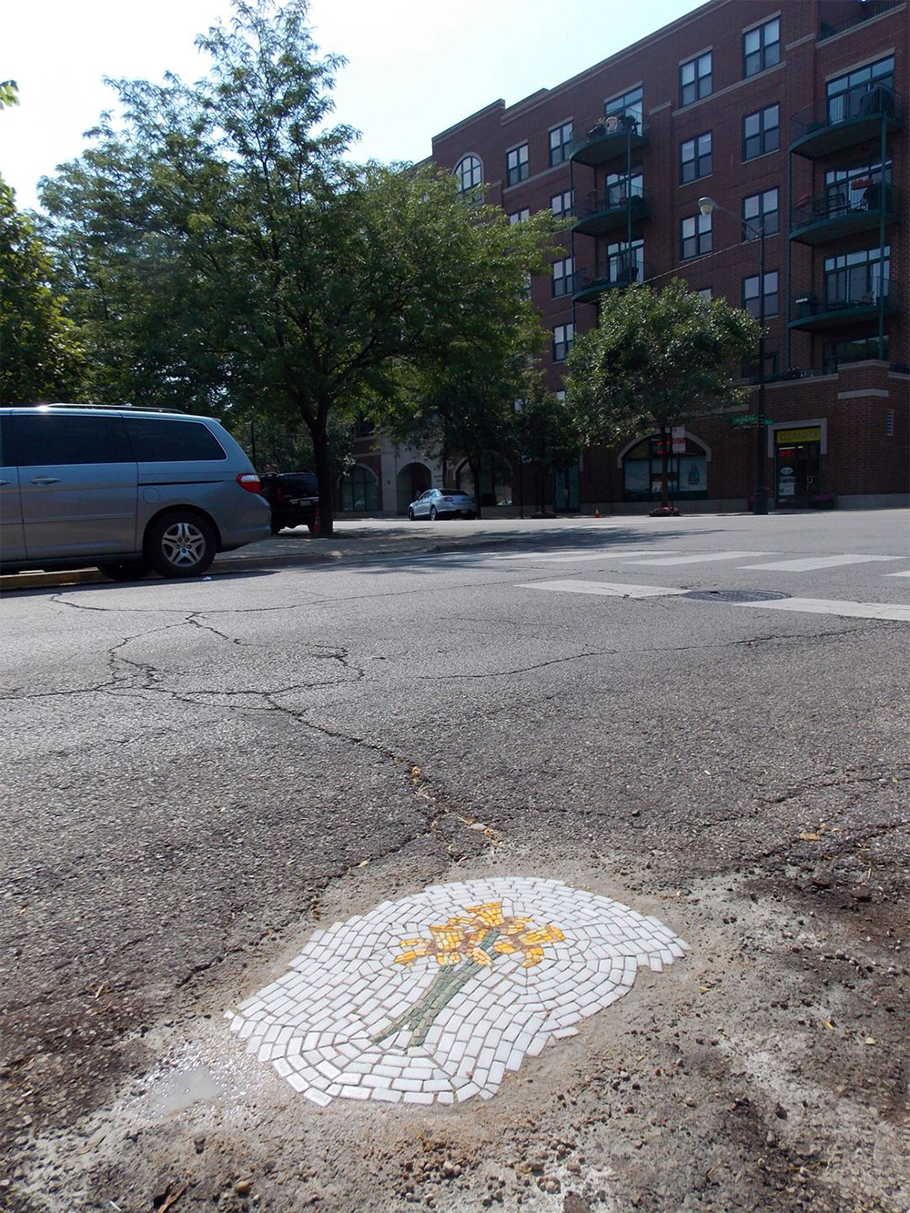 Guerilla Mosaic Artist Now Filling Chicago Potholes with Flowers street art mosaic flowers Chicago