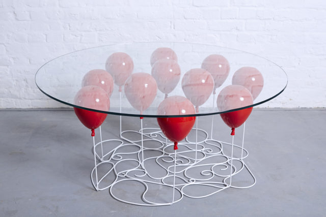 A Glass Table that Appears to be Held Aloft by Helium Balloons