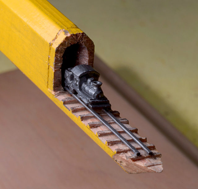 A Carved Graphite Train on Tracks Emerges from Inside a Carpenter's Pencil
