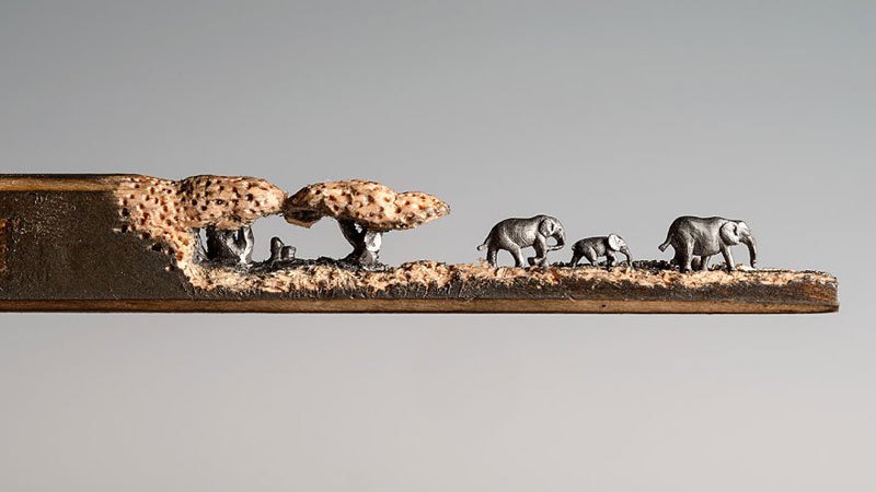 A miniature landscape of elephants carved from the tip