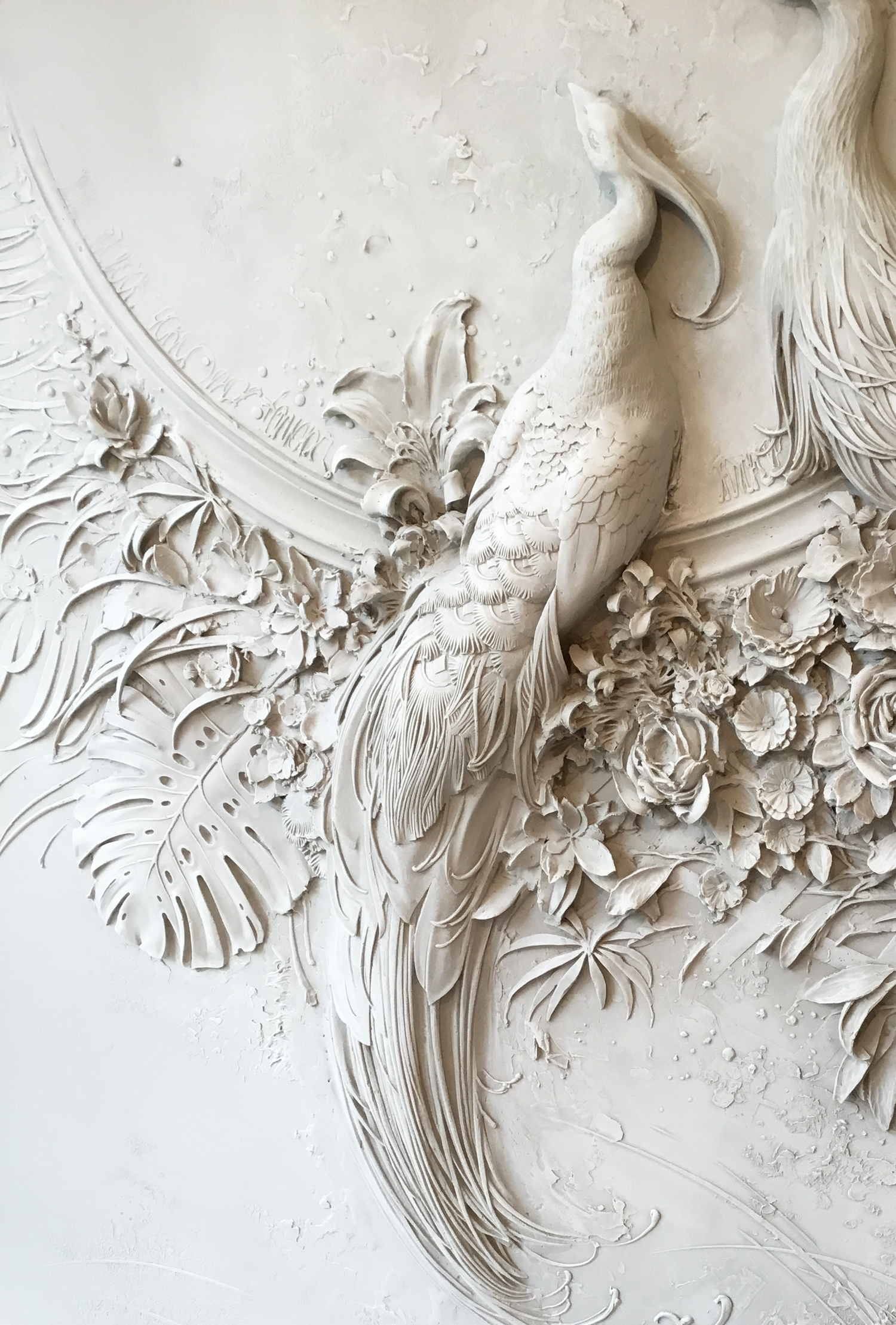 Interior bas relief sculptures of peacocks and lush florals by