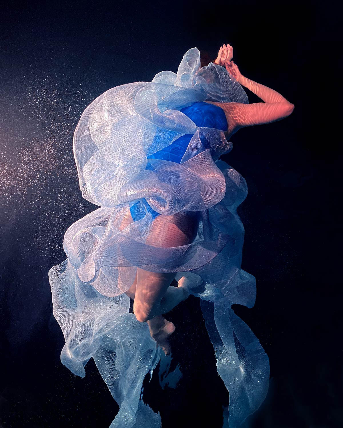 Swirling Fabrics Envelop Floating Subjects in Underwater Photographs by Christy Lee Rogers