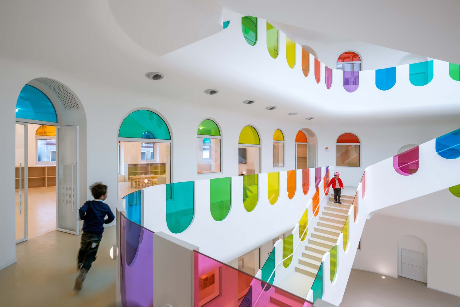 Hundreds of Rainbow Glass Panels Emit a Rotating Kaleidoscope in a Playful Kindergarten